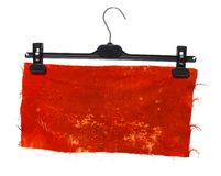 Plastic clothes hanger with hanging on it a piece of  clot. Plastic clothes hanger with hanging on it a piece of orange cloth Stock Image