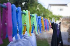 Plastic clothes pegs laying on the wire. royalty free stock images