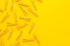Plastic clothes pegs. On the yellow background with copy space Stock Photo