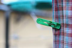 Plastic clothespin green pin and  chintz drying Royalty Free Stock Photo