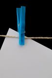 Plastic clothespin holding white paper on a wire Royalty Free Stock Photography
