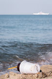Plastic coffee cup on the beach and white ship in the sea  backg Royalty Free Stock Photos
