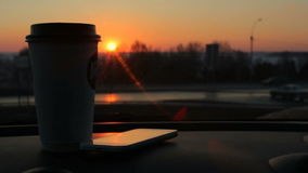 Plastic coffee cup, smartphone on car panel sunset city road traffic background stock video