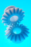 Plastic cogs. Two white cogwheels on blue background Royalty Free Stock Photo