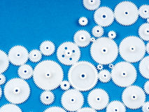 Plastic cogs. White plastic cogs on blue textured background, with copy space Royalty Free Stock Photography