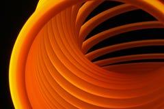 Plastic coil under blacklight. Orange plastic coil under blacklight Stock Photos