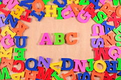Plastic colored letters ABC on a wooden background Royalty Free Stock Photos