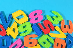 Plastic colored numbers on a blue background Stock Images