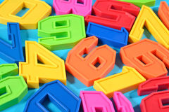 Plastic colored numbers on a blue background Royalty Free Stock Photo