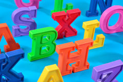 Plastic colorful alphabet letters close up on a blue Royalty Free Stock Photos