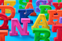 Plastic colorful alphabet letters close up on a blue Royalty Free Stock Photo