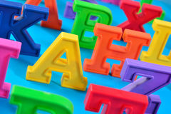 Plastic colorful alphabet letters close up on a blue Royalty Free Stock Images