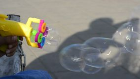 Plastic colorful bubble maker`s gun in young teenage hand in outdoor area. Child shadow on ground stock video footage