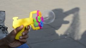 Plastic colorful bubble maker`s gun in young teenage hand in outdoor area. Child shadow on ground stock video