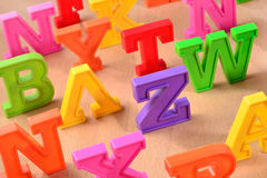Plastic colorful letters close up on a wooden background Stock Photos