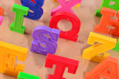 Plastic colorful letters close up on a wooden background Stock Images