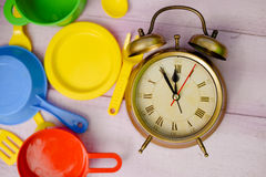 Plastic colorful toy dishware and vintage alarm Stock Photography