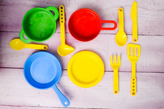 Plastic colorful toy dishware on wooden lilac Royalty Free Stock Photos