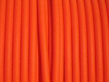 Plastic Conduit. Close up view of a large spool or bright orange flexible plastic conduit stock photography