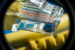 Plastic connector and yellow cable type twisted pair for connection to a computer network, macro abstract background. Plastic connector RJ45 and yellow cable UTP Stock Photography