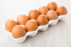 Plastic container with brown chicken eggs on table Stock Photo