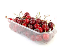 Plastic container with cherries. Over white background Royalty Free Stock Photos