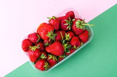 Plastic container with fresh strawberries royalty free stock photos