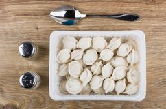 Plastic container with frozen dumplings, salt, pepper and spoon. On wooden table. Top view Stock Photo