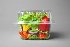 Plastic container with salad. On grey background royalty free stock photos