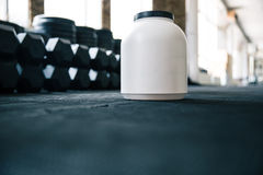 Plastic container with sports nutrition on dumbbells Stock Photo
