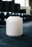 Plastic container with sports nutrition on dumbbells Royalty Free Stock Photography