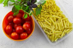 Plastic container with two types of pasta ,bowl with ripe tomatoes and fresh basil leaves. On white stone table royalty free stock photo
