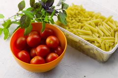 Plastic container with two types of pasta ,bowl with ripe tomatoes and fresh basil leaves royalty free stock images