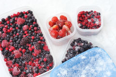 Plastic containers of frozen mixed berries in snow Royalty Free Stock Photography