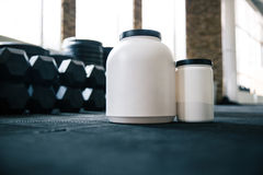 Plastic containers with sports nutrition on dumbbells Royalty Free Stock Images