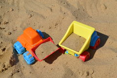 Plastic contruction toys in sand. Colorful plastic construction vehicles in sand Royalty Free Stock Photography