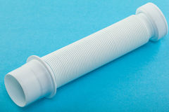 Plastic corrugated plumbing pipe. Closeup of plastic corrugated plumbing pipe on blue background Royalty Free Stock Photo