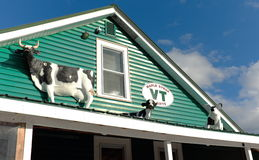 Plastic cows and a pig on a house roof. Stock Photos