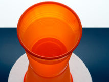 Plastic cup abstract. Bright orange disposable cup with water stock photos