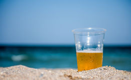 Plastic cup with beer. Plastic cup of beer, on the beach in sunlight Royalty Free Stock Photography
