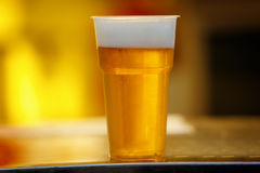 Plastic cup of beer, Disposable glass. Plastic cup of light beer standing on the table, Disposable glass stock images