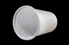 Plastic cup on black. White plastic cup isolated on a black background royalty free stock photography