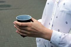 Plastic cup with coffee in a girl`s hand. Hand holds a brown plastic cup with coffee stock image
