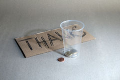 A plastic cup and coins Royalty Free Stock Images