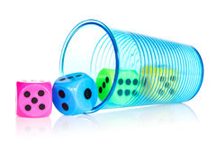 Plastic cup with colorful dice. Over a white background royalty free stock images