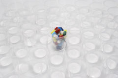 Plastic cup containing pills surrounded by empty glasses Stock Images