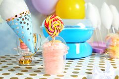Plastic cup with cotton candy and candies on table. At party stock photography