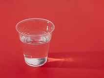 Plastic cup of fresh water over red,sidelit royalty free stock images