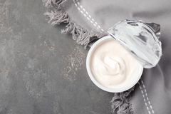 Plastic cup of fresh yogurt and napkin on grey background, top view. Space for text royalty free stock photo