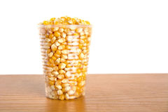 Plastic cup full of corn seeds on white Royalty Free Stock Images